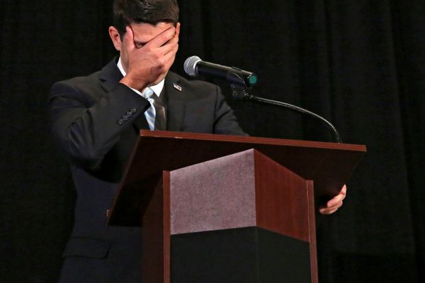 Image: U.S. Rep. Paul Ryan covers his faces as he tells a story during the Iowa GOP Lincoln Dinner in Cedar Rapids